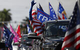 A man wearing a flag-themed body stocking waves from a car as hundreds of vehicles gather at Tropical Park ahead of a car caravan in support of US President Donald Trump, in Miami, November 1, 2020. (AP/Rebecca Blackwell)