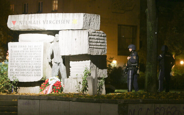 Police officers stay in position next to a memorial for victims of the Nazi era after gunshots were heard in Vienna, November 2, 2020. (Photo/Ronald Zak)