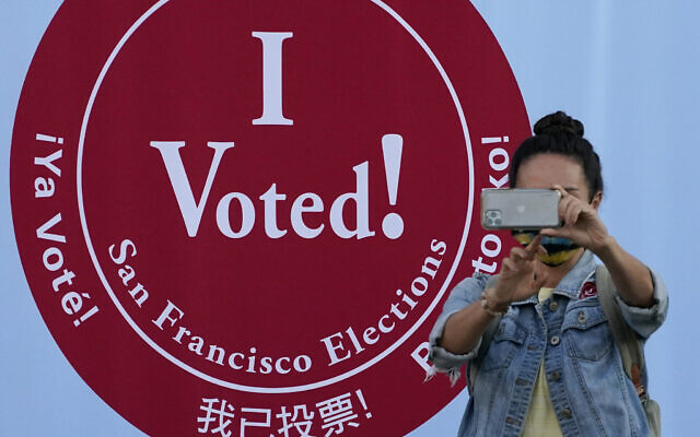 A woman takes a photo in front of an I Voted sign at a San Francisco Department of Elections voting center in San Francisco, Monday, Nov. 2, 2020, ahead of Election Day. (AP Photo/Jeff Chiu)