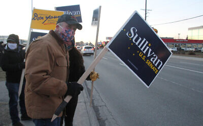 US Sen. Dan Sullivan, an Alaska Republican seeking reelection, waves a sign at a busy intersection on November 2, 2020, in Anchorage, Alaska. (AP Photo/Mark Thiessen)