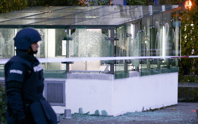 A police officer patrols in front of an entrance of a car park with broken glasses after a shooting in Vienna, Austria, Nov. 3, 2020 (AP Photo/Ronald Zak)