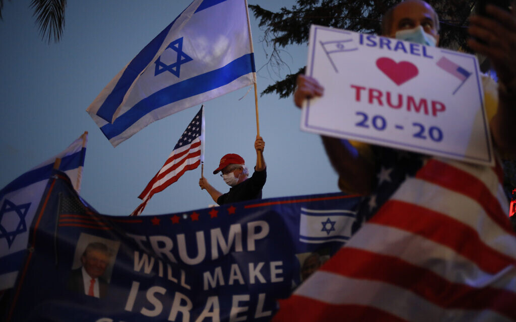 Supporters of US President Donald Trump wave Israeli and US national flags in Carmiel, northern Israel, Tuesday, November 3, 2020. (AP/Ariel Schalit)