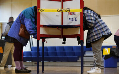 Caution tape closes off a voting stall to help distance voters to help prevent the spread of the coronavirus during Election Day at the East End School, November 3, 2020, in Portland, Maine. (AP Photo/Robert F. Bukaty)