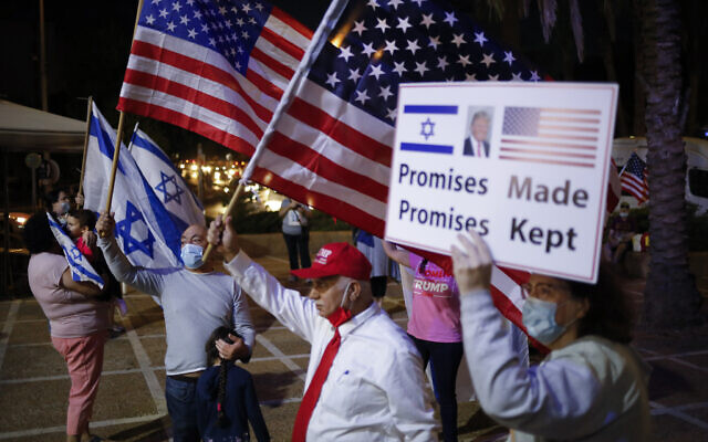 Supporters of US President Donald Trump wave Israeli and US national flags and carry placards in support, on the day of the US presidential election, in Carmiel, northern Israel, Tuesday, Nov. 3, 2020. (AP/Ariel Schalit)