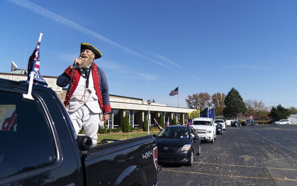 Trump supporter Matthew Woods, dressed as a Continental Army soldier, leads a Trump Train Rally through the parking lot of a polling precinct on Election Day in Warren, Michigan, Tuesday, November 3, 2020. (AP/David Goldman)