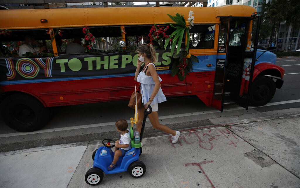 """Pedestrians pass by a bus, where """"Joy to the Polls"""" volunteers were playing music to liven up a polling station in downtown Miami, on Election Day, Tuesday, Nov. 3, 2020.(AP/Rebecca Blackwell)"""