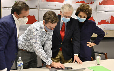Republican Senate candidate Sen. Mitch McConnell, second from right, and his wife, Elaine Chao, right, look on as aides show him the election results in Louisville, Kentucky, Nov. 3, 2020. (AP Photo/Timothy D. Easley)