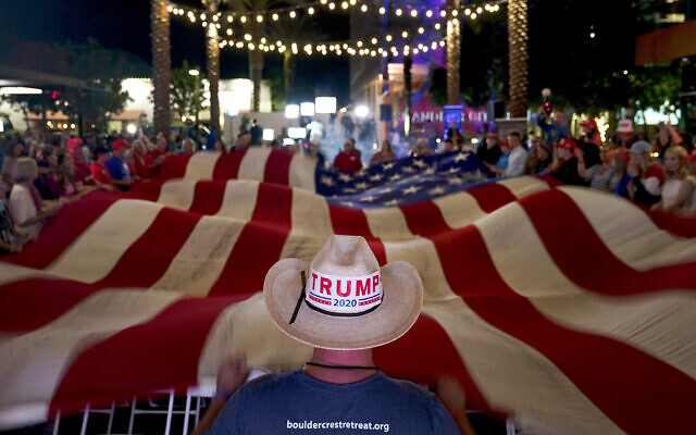 US President Donald Trump supporters wave a flag during an election watch party, Nov. 3, 2020, in Chandler, Arizona (AP Photo/Matt York)