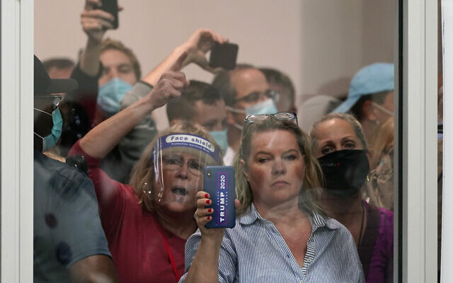 People wanting to be election challengers yell as they look through the windows of the central counting board as police were helping to keep additional challengers from entering due to overcrowding, November 4, 2020, in Detroit. (AP Photo/Carlos Osorio)