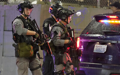 Illustrative: Police officials stand guard during a protest after the Nov. 3 elections, Wednesday, Nov. 4, 2020, in Seattle. (AP Photo/Ted S. Warren)