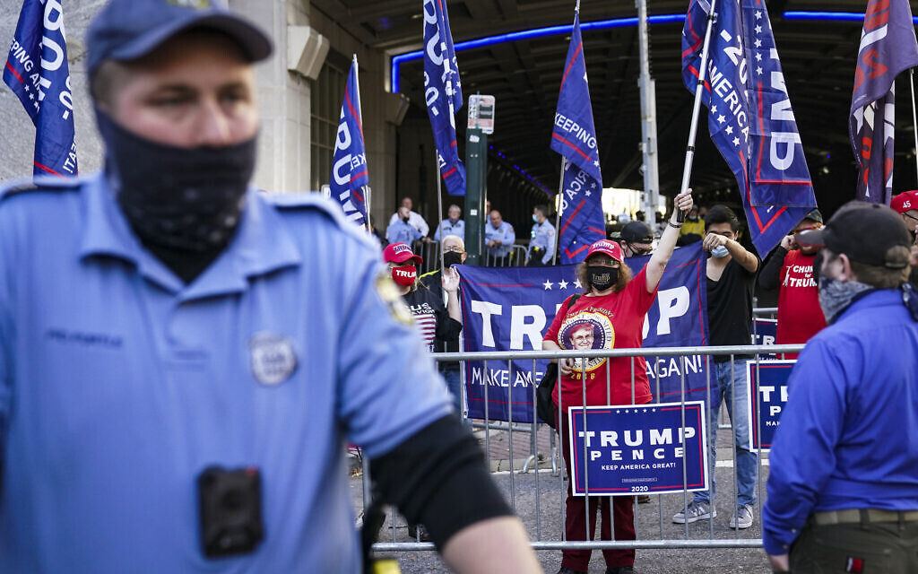 Police separate US President Donald Trump supporters and pro-vote counting demonstrators outside the Philadelphia Convention Center three days after the presidential election polls closed as they await tabulation results, Friday, Nov. 6, 2020, in Philadelphia. (AP Photo/John Minchillo)