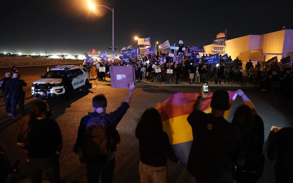 Supporters of Democratic presidential candidate former Vice President Joe Biden, below, protest across from supporters of President Donald Trump, above, in front of the Clark County Election Department, Nov. 6, 2020, in North Las Vegas, Nevada. (AP Photo/Jae C. Hong)