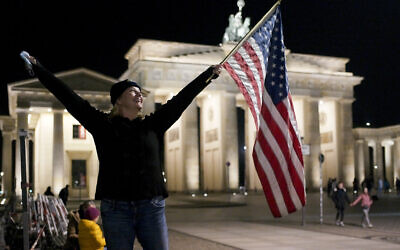 Marianne Hoenow from Connecticut in the US celebrates the victory of President-elect Joe Biden and Vice President-elect Kamala Harris in front of the Brandenbug Gate next to the United States embassy in Berlin, Germany, Saturday, Nov. 7, 2020. (AP/Markus Schreiber)