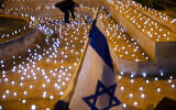 A man turns on LED candles at a memorial for Israel's victims of COVID-19, in Jerusalem, Sunday, Nov. 8, 2020. (AP Photo/Oded Balilty)