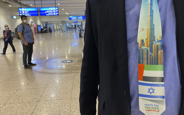 An Israeli tourist wears a souvenir tie with a first flight sign and the flags of Israel and the UAE after landing at Dubai Airport, in the United Arab Emirates, Sunday, Nov. 8, 2020. (AP/Malak Harb)