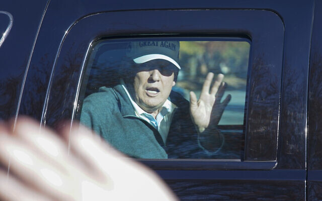 US President Donald Trump waves to supporters as he departs after playing golf at the Trump National Golf Club in Sterling Va., Sunday Nov. 8, 2020. (AP Photo/Steve Helber)