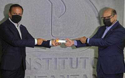 Sao Paulo Governor Joao Doria, left, and Butantan Institute Director Dimas Covas hold up a box of an experimental COVID-19 vaccine that is being tested in partnership with China's pharmaceutical company Sinovac during a press conference in Sao Paulo, Brazil, November 9, 2020. (AP Photo/Andre Penner)