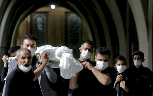 Mourners carry the body of a person who died from COVID-19 at the Behesht-e-Zahra cemetery on the outskirts of Tehran, Iran, Nov. 1, 2020 (AP Photo/Ebrahim Noroozi)