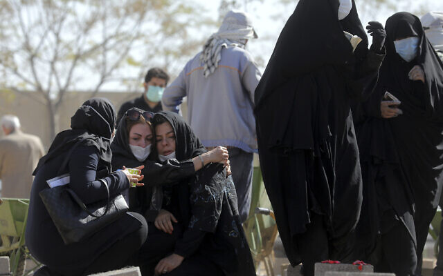 Mourners attend the funeral of a person who died from COVID-19 at the Behesht-e-Zahra cemetery just outside Tehran, Iran, Nov. 1, 2020 (AP Photo/Ebrahim Noroozi)