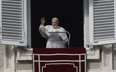 Pope Francis salutes the faithful from his studio's window as he recites the Angelus prayer in St. Peter's square at the Vatican, Sunday, Nov. 15, 2020. (AP Photo/Gregorio Borgia)