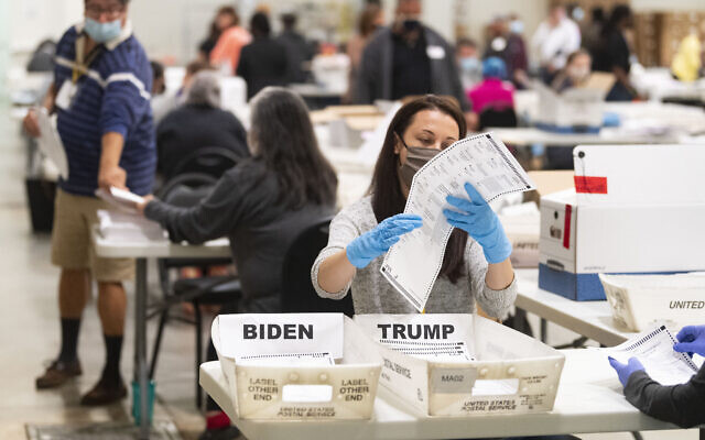 An election worker looks at a ballot during a Cobb County hand recount of Presidential votes on Nov.15, 2020, at the Miller Park Event Center in Marietta, Ga. (JOHN AMIS FOR THE ATLANTA JOURNAL-CONSTITUTION)