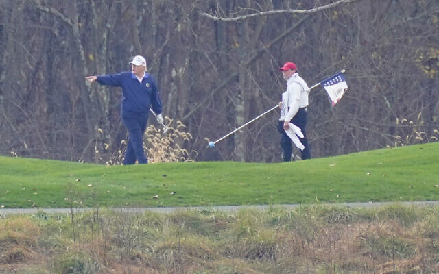 US President Donald Trump, left, gesturing while playing golf at Trump National Golf Club in Sterling, Virginia, November 15, 2020. (Manuel Balce Ceneta/AP)