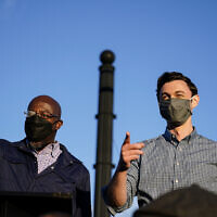 Georgia Democratic candidates for US Senate Raphael Warnock, left, and Jon Ossoff, right, gesture toward a crowd during a campaign rally on November 15, 2020, in Marietta, Ga. (AP/Brynn Anderson)