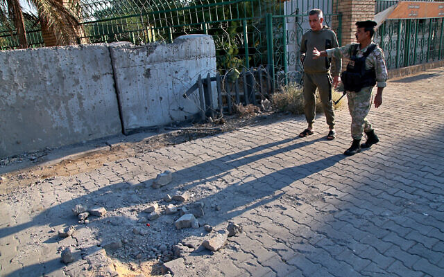 Security forces inspect the scene of the rocket attack at the gate of al-Zawra public park in Baghdad, Iraq, November 18, 2020. (AP Photo/Khalid Mohammed)