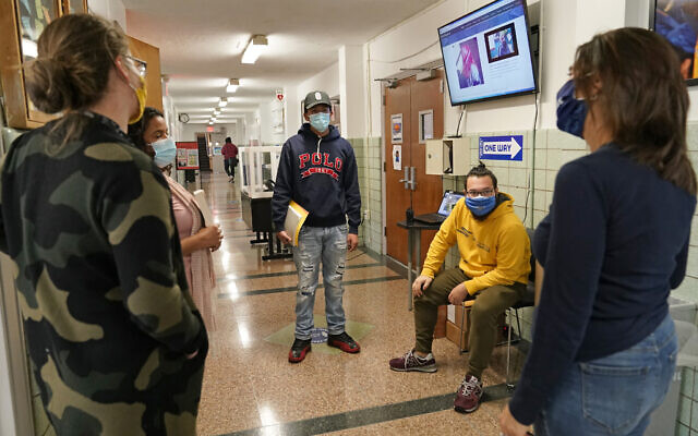 Teachers Alis Anasal, from left, and Grimaldy Ortiz, join student Jovanny Mendez, center, advocate counselor Christian Velsaco, and Good Shepherd Services director Karen Dette as they chat in the hallway at West Brooklyn Community High School after learning that the school would be closing for the third time this year due to the city's attempt to control the spread of coronavirus, Wednesday, Nov. 18, 2020, in the Brooklyn borough of New York. The mayor and schools chancellor announced Wednesday that school buildings will close Thursday. (AP Photo/Kathy Willens)
