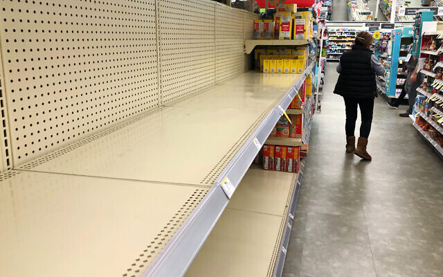 Shelves in the toilet paper aisle at a Walgreens store sit empty in Buffalo Grove, Ill., Wednesday, Nov. 18, 2020. A surge of new coronavirus cases in the US is sending people back to stores to stockpile again, leaving shelves bare and forcing retailers to put limits on purchases. (AP Photo/Nam Y. Huh)
