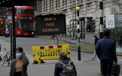 A sign is displayed outside Waterloo train station to remind people thy are required to wear face coverings inside the station and whilst travelling on trains during England's second coronavirus lockdown, in London, Friday, Nov. 20, 2020.  Britain yesterday registered 501 daily COVID-19 deaths within 28 days of a positive test and is the fifth country in the world to record more than 50,000 coronavirus-related deaths. (AP Photo/Matt Dunham)