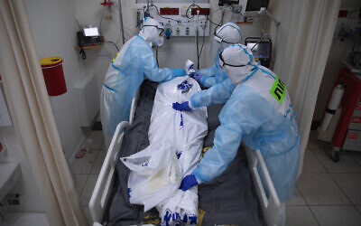 Medical personnel wearing protective equipment cover the body of a man who died from COVID-19, in the intensive care ward for coronavirus patients at Shaare Zedek Medical Center in Jerusalem, November 23, 2020. (AP Photo/Oded Balilty)