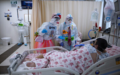 Clowns wearing protective equipment entertain a COVID-19 patient in the intensive care ward for coronavirus patients at Shaare Zedek Medical Center in Jerusalem, Nov. 23, 2020. (AP Photo/Oded Balilty)