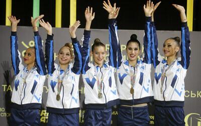 Israel's rhythmic gymnastics team wave from the podium before receiving their gold medals during the 36th European Rhythmic Gymnastics Championships in Kyiv, Ukraine, Friday, Nov. 27, 2020 (AP Photo/Efrem Lukatsky)