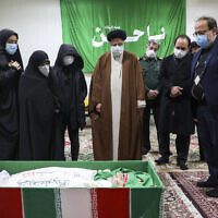 Iran's Judiciary Chief Ayatollah Ebrahim Raisi pays his respect to the body of slain scientist Mohsen Fakhrizadeh among his family, in Tehran, Iran, November 28, 2020. (Mizan News Agency via AP)