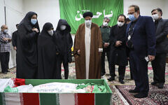 Iran's Judiciary Chief Ayatollah Ebrahim Raisi pays his respect to the body of slain scientist Mohsen Fakhrizadeh among his family, in Tehran, Iran, Saturday, Nov. 28, 2020 (Mizan News Agency via AP)