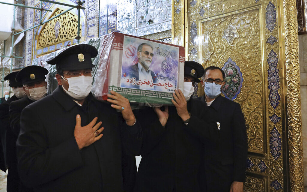 In this picture released by the Iranian Defense Ministry and taken on Saturday, Nov. 28, 2020, caretakers from the Imam Reza holy shrine, carry the flag draped coffin of Mohsen Fakhrizadeh, an Iranian scientist linked to the country's disbanded military nuclear program, who was killed on Friday, during a funeral ceremony in the northeastern city of Mashhad, Iran.  (Iranian Defense Ministry via AP)