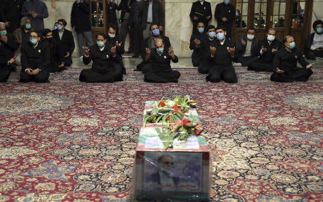 In this picture released by the Iranian Defense Ministry and taken on Saturday, Nov. 28, 2020, people pray over the flag draped coffin of Mohsen Fakhrizadeh, an Iranian scientist linked to the country's military nuclear program,(Iranian Defense Ministry via AP)