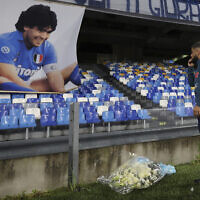 Napoli's Lorenzo Insigne lays a bouquet of flowers under a photo of Diego Armando Maradona exposed at the San Paolo stadium, November 29, 2020, prior to the Italian Serie A soccer match between Napoli and Roma, in Naples, Italy. (Alessandro Garofalo/LaPresse via AP)