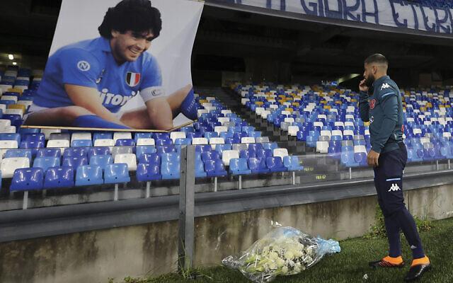 Napoli's Lorenzo Insigne lays a bouquet of flowers under a photo of Diego Armando Maradona exposed at the San Paolo stadium, November 29, 2020, prior to the Italian Serie A soccer match between Napoli and Roma, in Naples, Italy. (Alessandro Garofalo/LaPresse via AP)