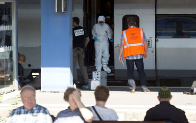 People wait for a train in the foreground as members of a police forensics team take part in an investigation next to a Thalys train on the platform at Arras train station, northern France, August 22, 2015. (Virginia Mayo/AP)