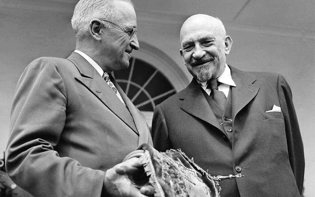 US president Harry S. Truman holds a copy of the Torah, presented to him by Chaim Weizmann, right, in Washington, May 25, 1948. (AP Photo)