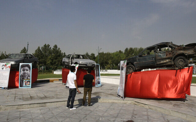 Damaged cars that three Iranian scientists, Masoud Ali Mohammadi, right, Majid Shahriari, center, and Mostafa Ahmadi Roshan, were riding in when they were killed in bombings are displayed outside a conference hall hosting the meeting of Non-Aligned Movement, NAM, in Tehran, Iran, Sunday, Aug. 26, 2012 (AP Photo/Vahid Salemi)