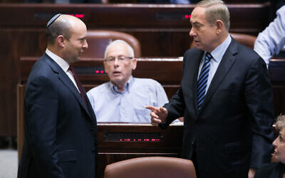 Prime Minister Benjamin Netanyahu, right, speaks with then Education Minister Naftali Bennett during a plenum session in the Knesset, on December 5, 2016. (Yonatan Sindel/Flash90)