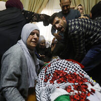 Relatives of Ahmad Jamal Manasra, 26, mourn near his body during his funeral ceremony in the West Bank village of Wad Fokin, near Bethlehem on March 21, 2019, Manasra was shot dead an Israeli soldier at Al-Nashash military checkpoint near the West Bank city Bethlehem. ( Wisam Hashlamoun/Flash90)