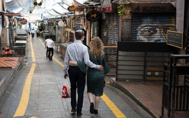 Illustrative: A couple walks in Jerusalem's Mahane Yehuda market on September 25, 2020, during a nationwide lockdown to prevent the spread of COVID-19. (Nati Shohat/Flash90)