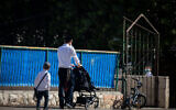 An ultra-Orthodox boy walks with his father to a Talmud Torah school in the Sanhedrin neighborhood in Jerusalem, October 18, 2020. (Yonatan Sindel/Flash90)