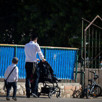 An ultra-Orthodox boy walks with his father to a Talmud Torah school in the Sanhedrin neighborhood in Jerusalem, October 18, 2020. (Yonatan Sindel/Flash90)