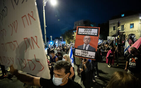 "A protester holds up a sign of Netanyahu, alongside the caption: ""1995: The murder of Yitzhak Rabin. 2020: the murder of democracy"" in Jerusalem, on October 31, 2020. (Yonatan Sindel/Flash90)"