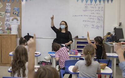 Illustrative -- Israeli children wearing face masks study in a classroom of the Kramim school in Jerusalem on their first day back to classes on November 1, 2020 (Olivier Fitoussi/Flash90)